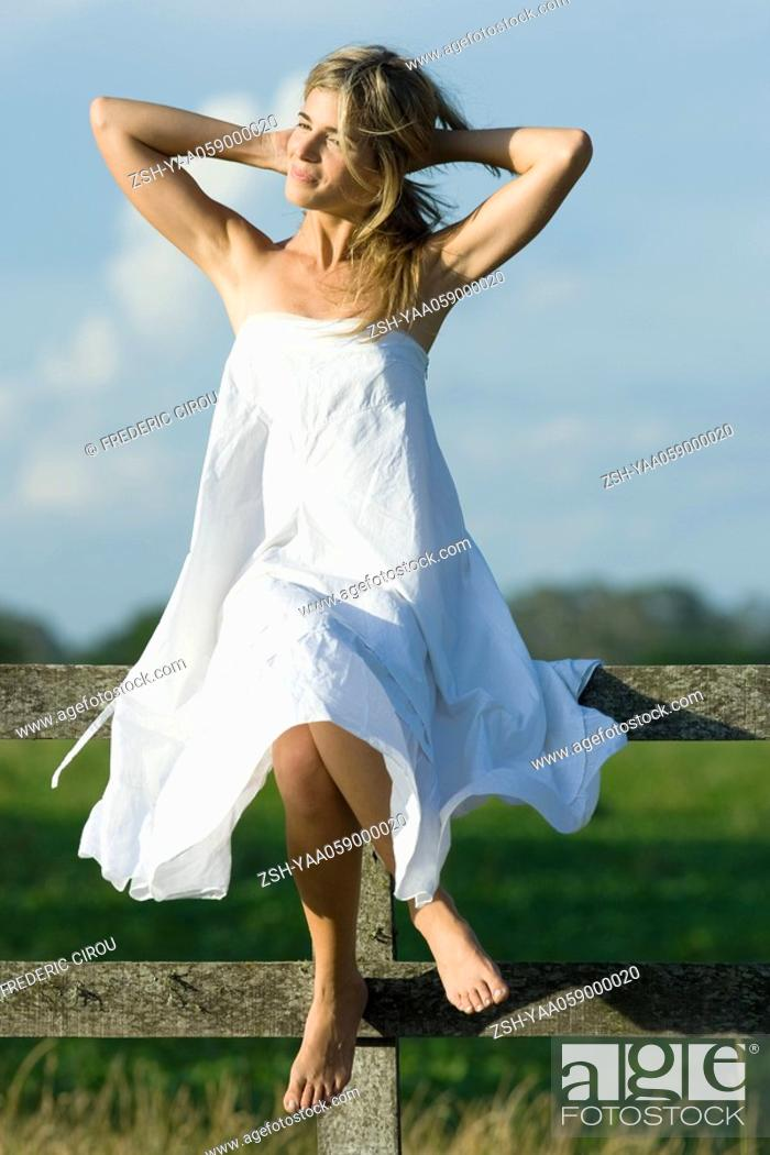 Stock Photo: Young woman sitting on top of wooden fence, hands behind neck, smiling.