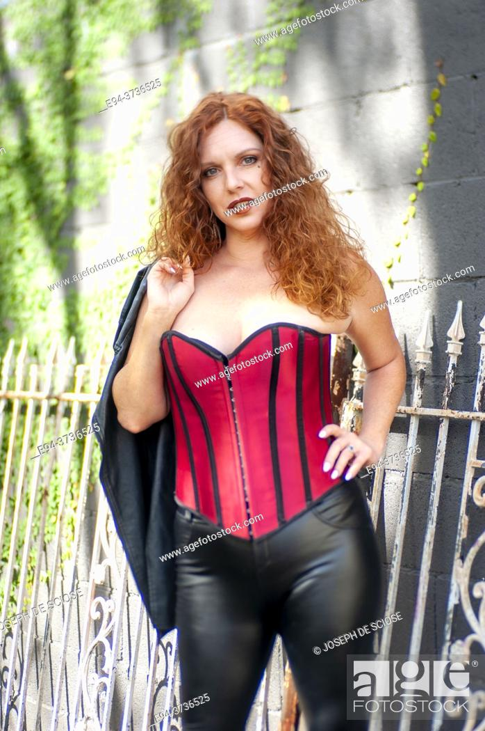 Stock Photo: A 41 year old redheaded woman wearing a red bustier and black leather pants.
