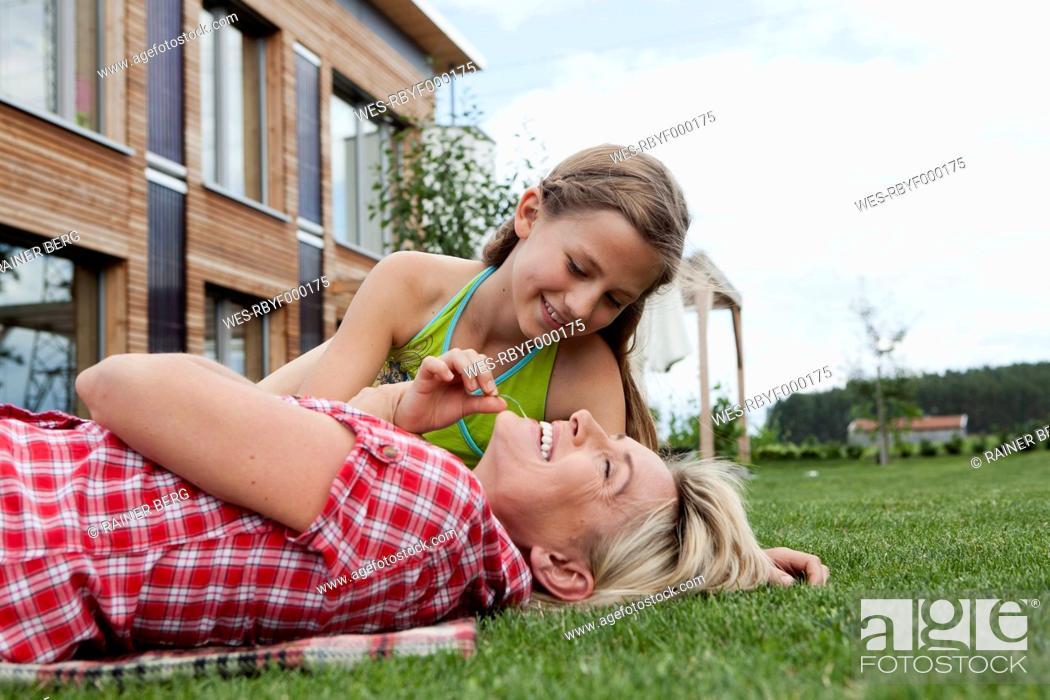 Stock Photo: Germany, Bavaria, Nuremberg, Mother and daughter having fun in garden.