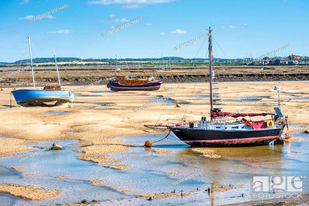 Stock Photo: Colourful boats marooned on sandbanks at low tide on East Fleet river estuary at Wells next the sea, North Norfolk coast, East Anglia, England, UK.