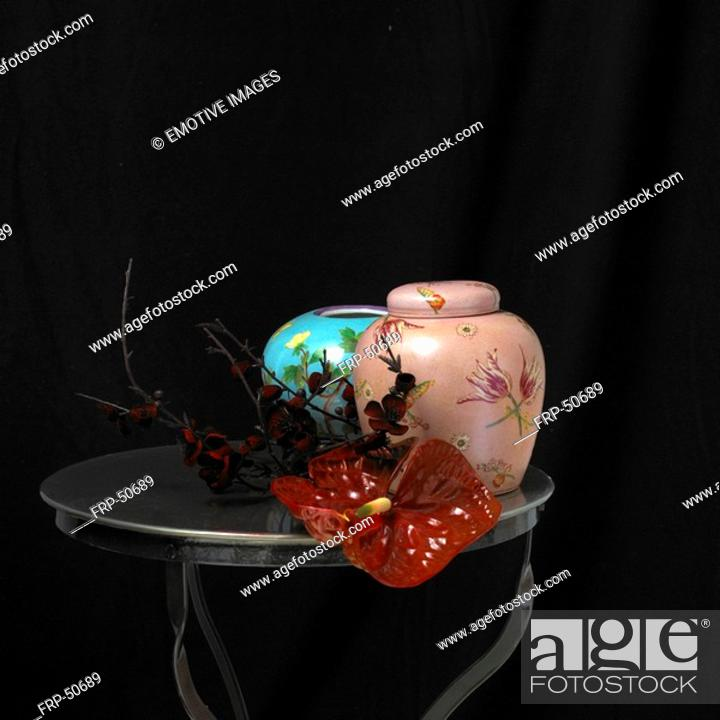 Stock Photo: Vase, urn and flamingo flower on a small table.