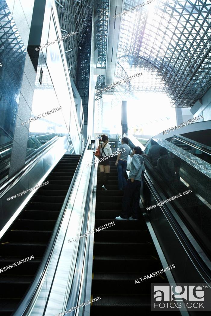 Stock Photo: People going up escalator, rear view.