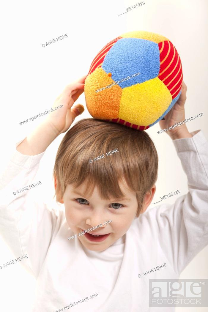 Stock Photo: boy holding ball on head, white background, isolated.