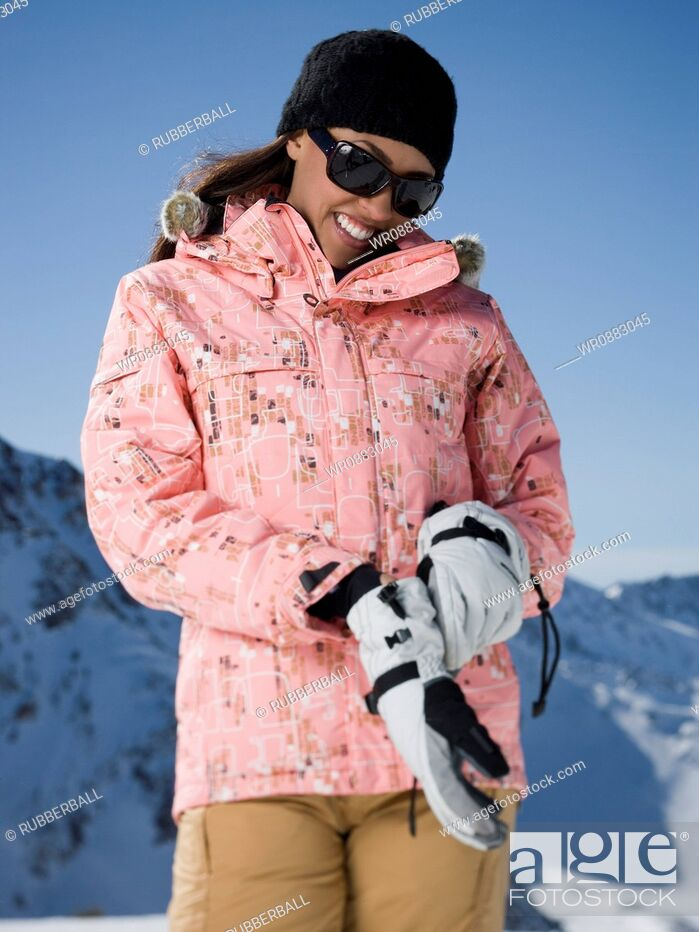 Stock Photo: Low angle view of a young woman putting on gloves.