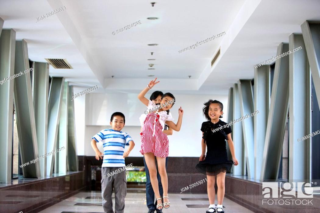 Stock Photo: Child, Children jumping on the corridor with teacher standing behind.