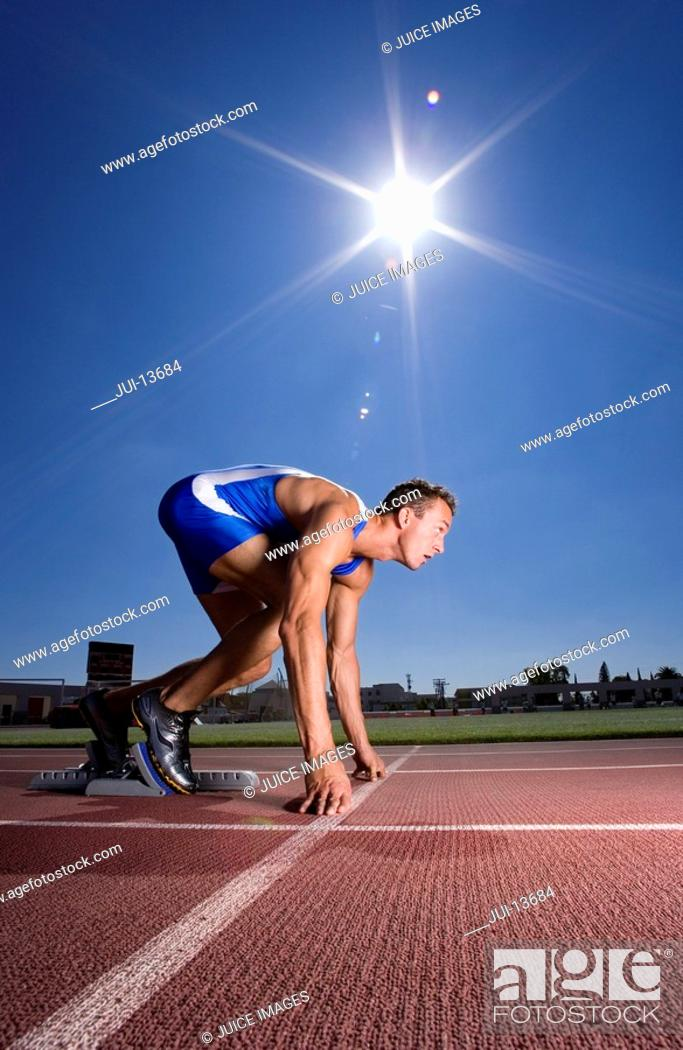 Stock Photo: Male sprinter on starting block, side view sun flare.