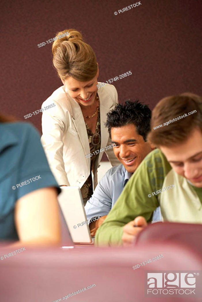 Stock Photo: Professor looking at a laptop of a college student in a lecture hall and smiling.