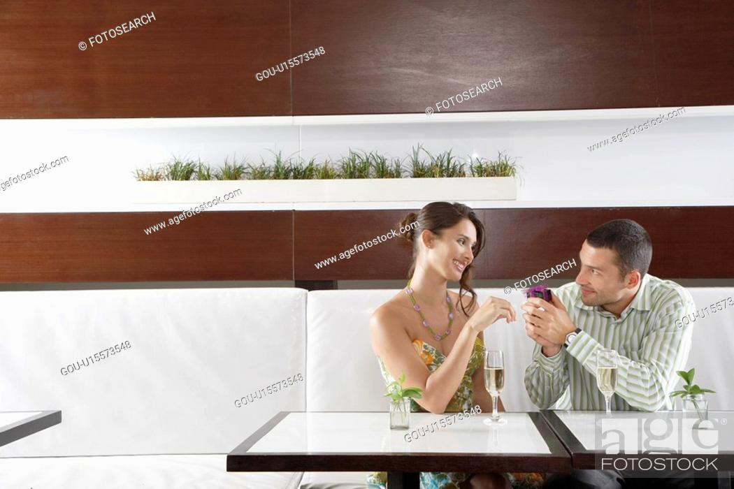 Stock Photo: Man giving woman gift in restaurant.