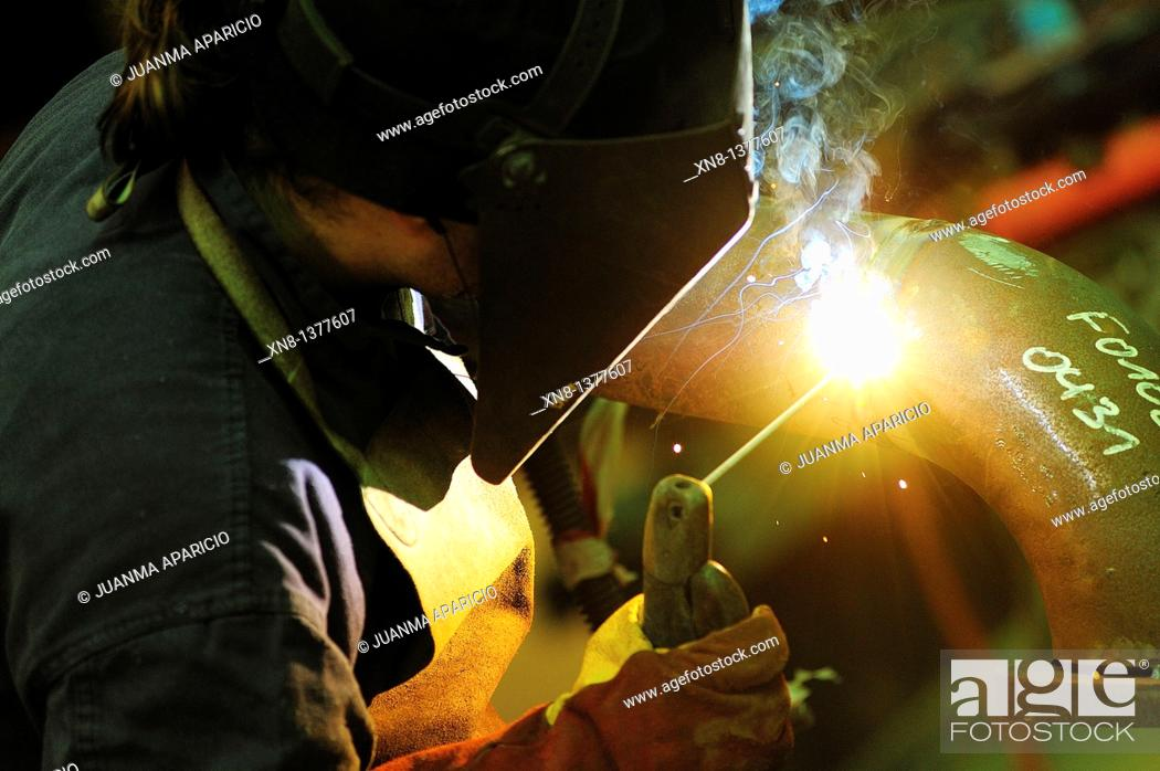 Stock Photo: Metal worker making a weld in a pipe.