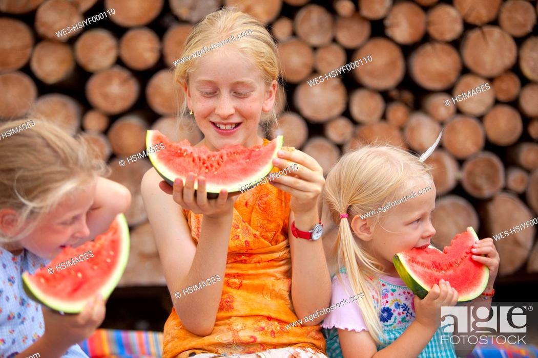 Stock Photo: Germany, Bavaria, Girls eating watermelon.
