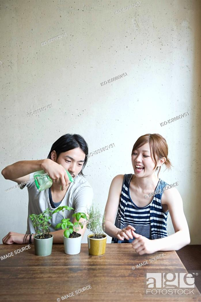 Stock Photo: Young couple with plant.
