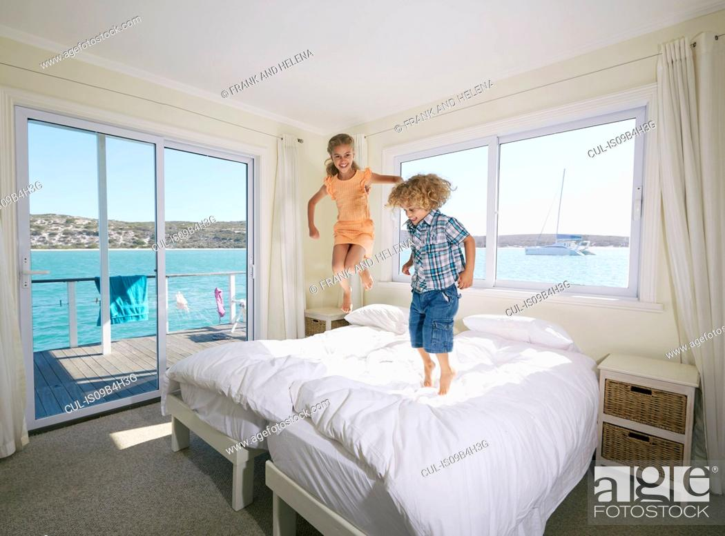 Stock Photo: Boy and girl jumping on bed in houseboat, Kraalbaai, South Africa.
