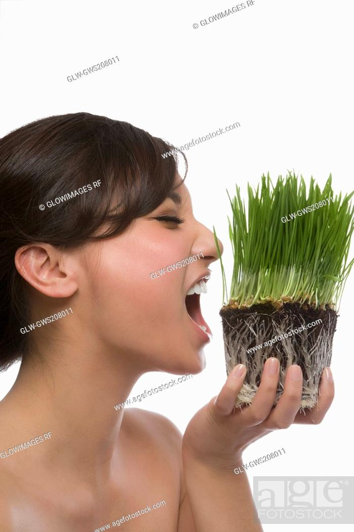 Stock Photo: Close-up of a young woman eating wheatgrass.