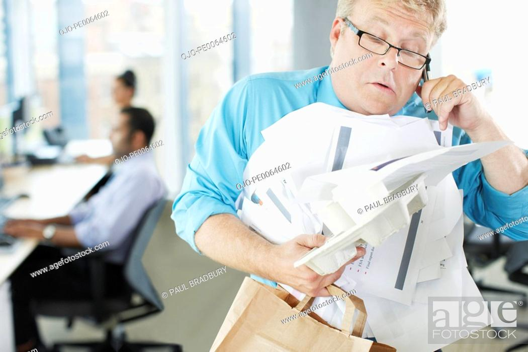 Stock Photo: Businessman talking on phone holding paperwork and coffee.