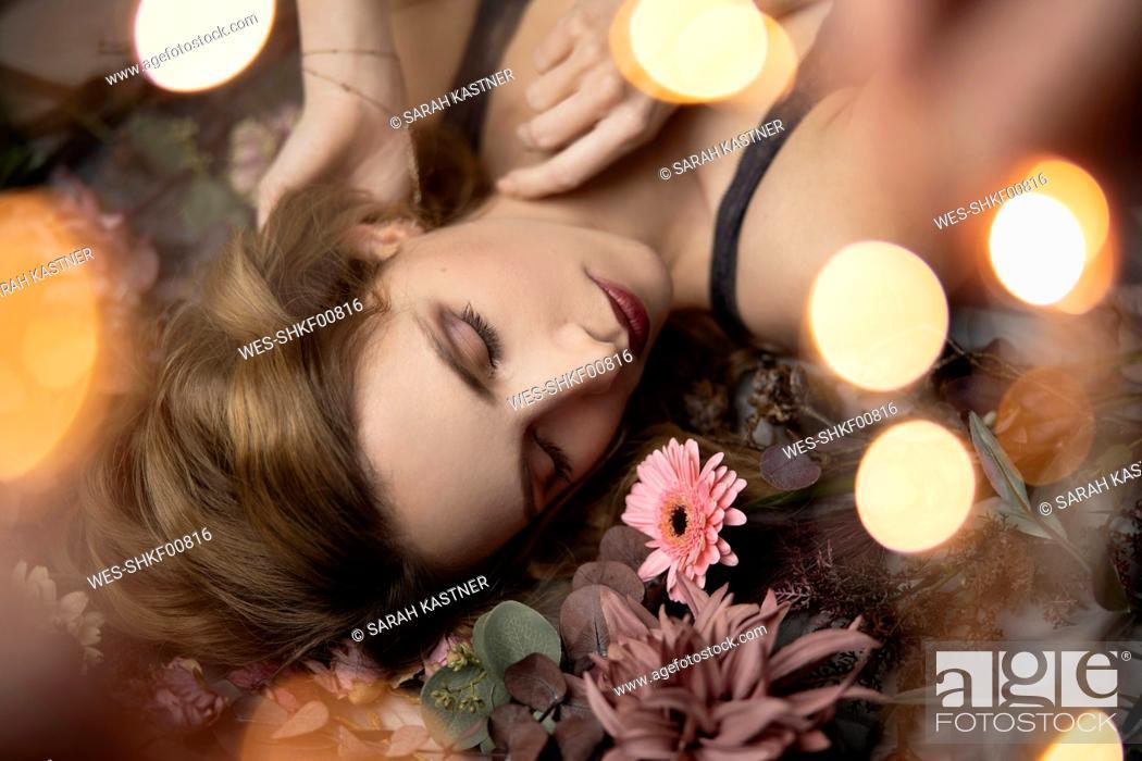 Stock Photo: Beautiful woman lying on flowers, close up.