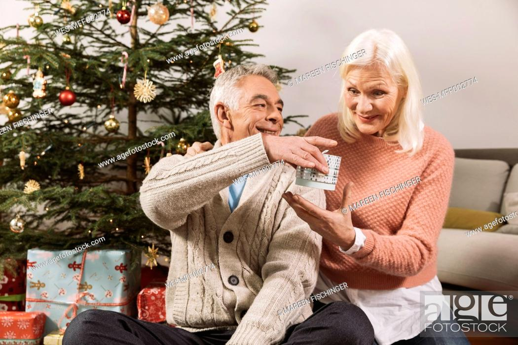 Stock Photo: Senior couple exchanging Christmas gifts in front of tree.