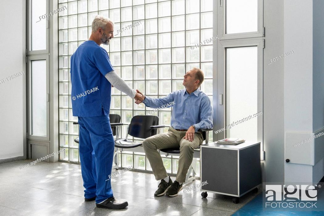 Stock Photo: Doctor greeting, shaking hands with patient in clinic waiting room.