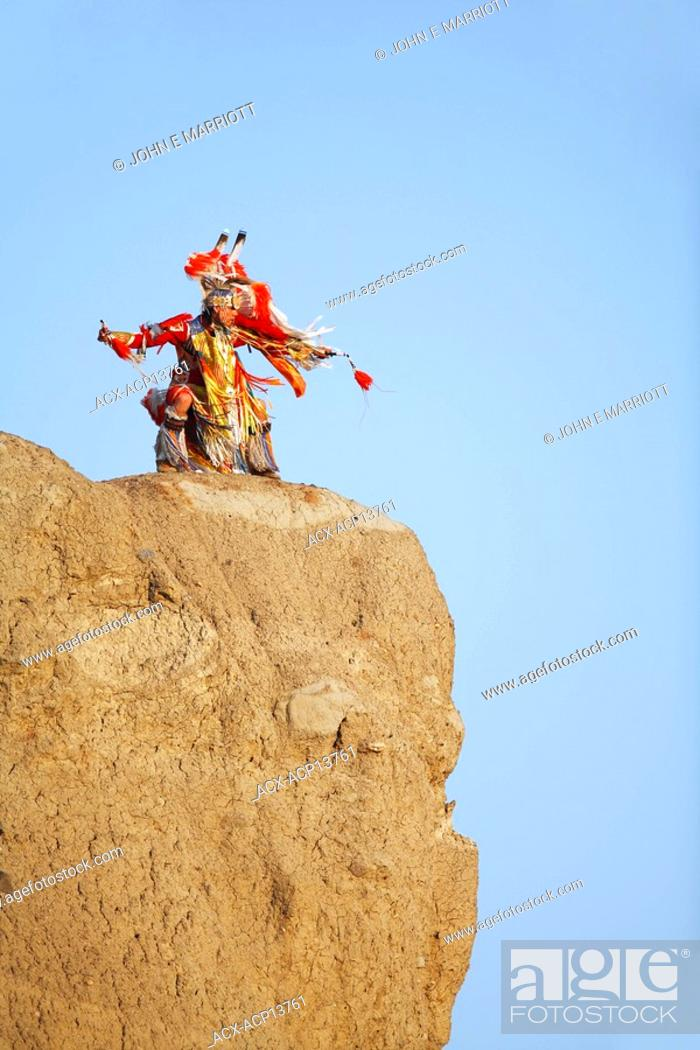 Stock Photo: Blackfoot Blood Plains Indians man on a cliff in traditional mens fancy dance outfit, Indian Battle Provincial Park, Lethbridge, Alberta, Canada.