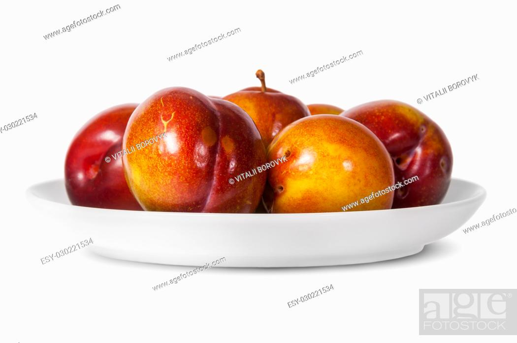 Stock Photo: In front red and yellow plums on white plate isolated on white background.