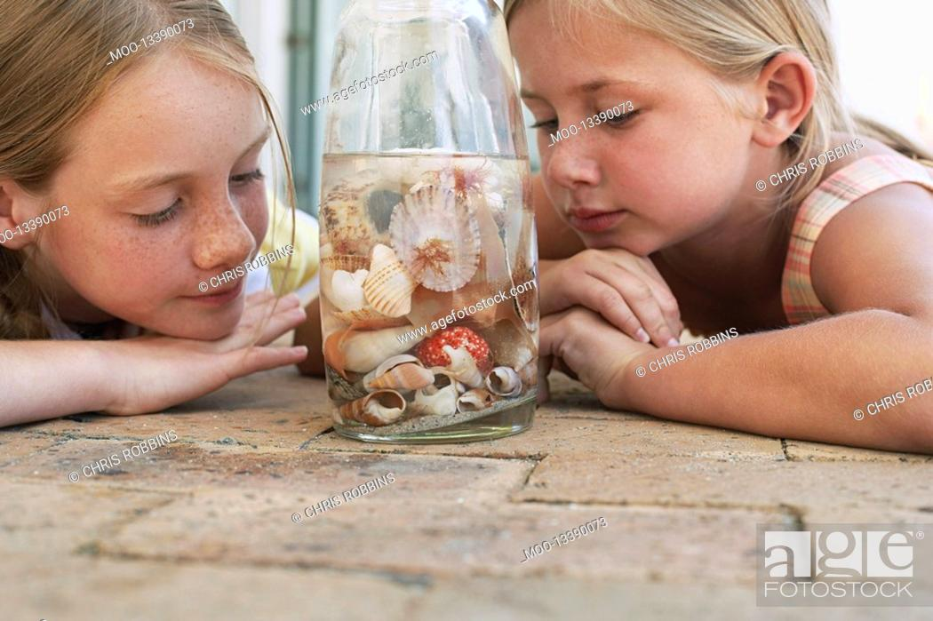 Stock Photo: Two girls 7-9 10-12 looking at shells in jar close-up.