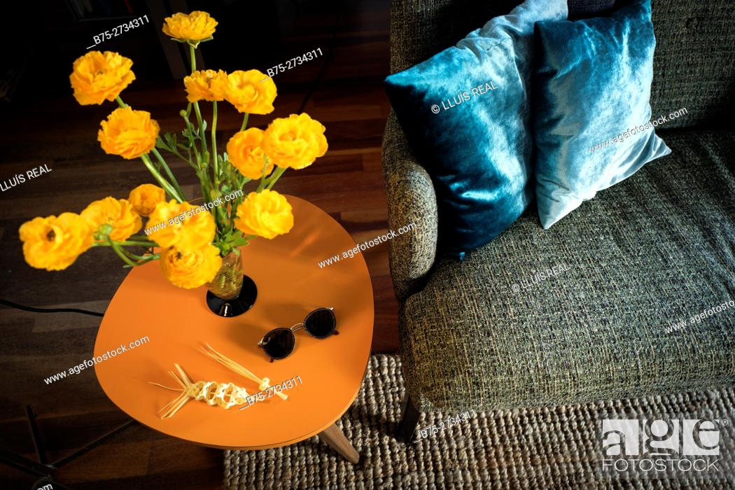 Stock Photo: Coffee table with a vase with yellow flowers, a pair of sunglasses and two miniature Easter palms. Part of a sofa with two blue cushions.