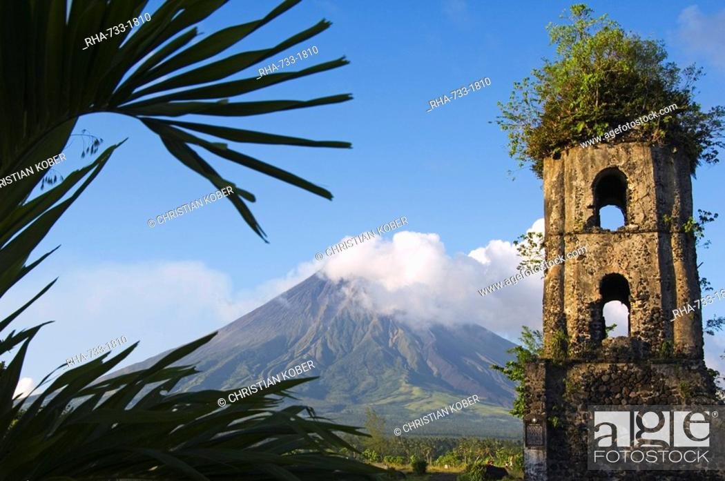 Stock Photo: Church belfry ruins and volcanic cone with smoke plume of Mount Mayon, 2462m, Cagsawa, where 1200 people were buried alive in 1814 eruption, Bicol Province.