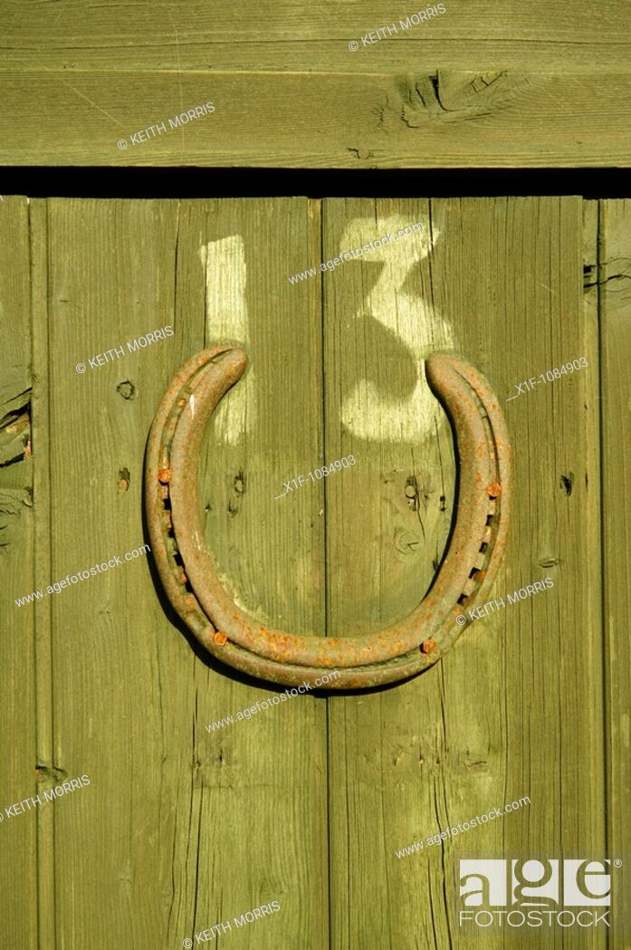 Stock Photo: Unlucky number 13 with lucky horseshoe on wooden door on an allotment garden shed, Aberystwyth Wales UK.