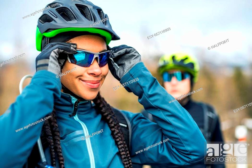 Stock Photo: Two mountain bikers standing on road outdoors in winter, putting on sunglasses.