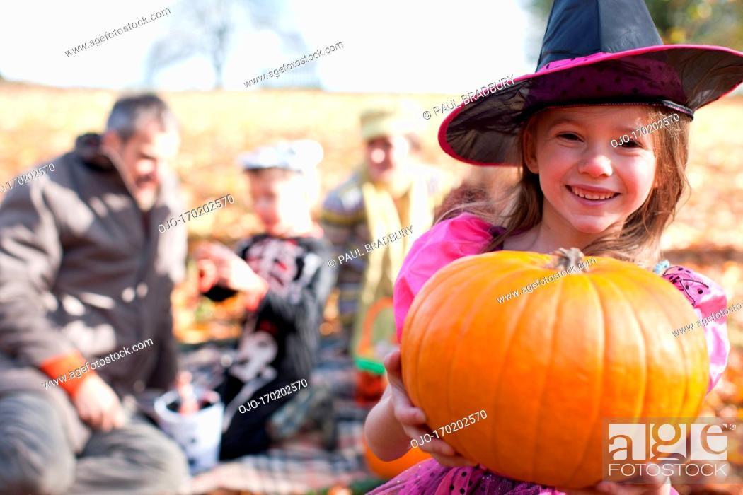 Stock Photo: Girl in Halloween costumes holding pumpkin.