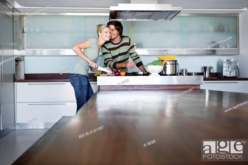 Stock Photo: Young couple in modern kitchen, cooking together, kissing, smiling.