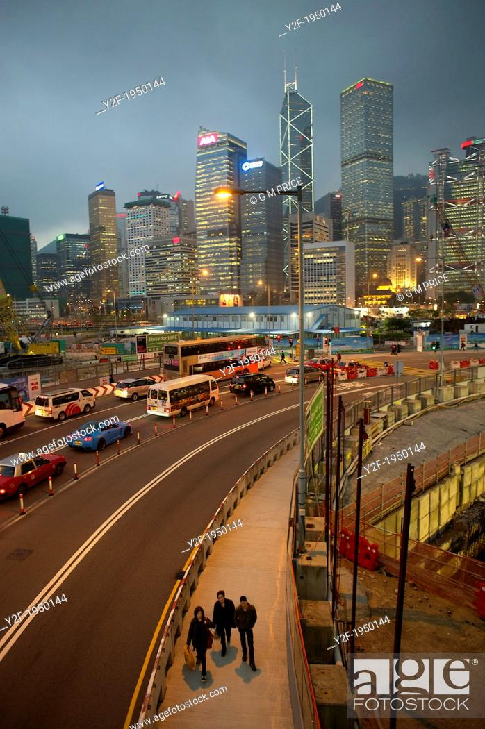 Stock Photo: people and traffic pass through Central Hong Kong construction zone at dusk.