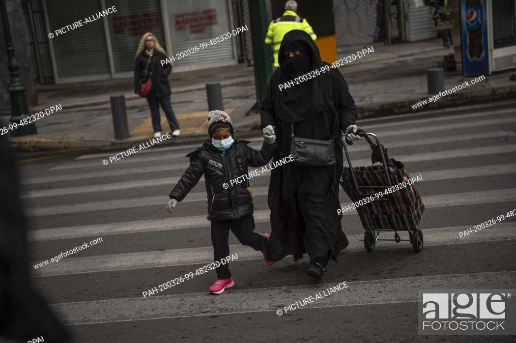 Imagen: 26 March 2020, Greece, Athen: A migrant holds a child by the hand. Greece also has extensive exit restrictions nationwide to contain the spread of coronavirus.