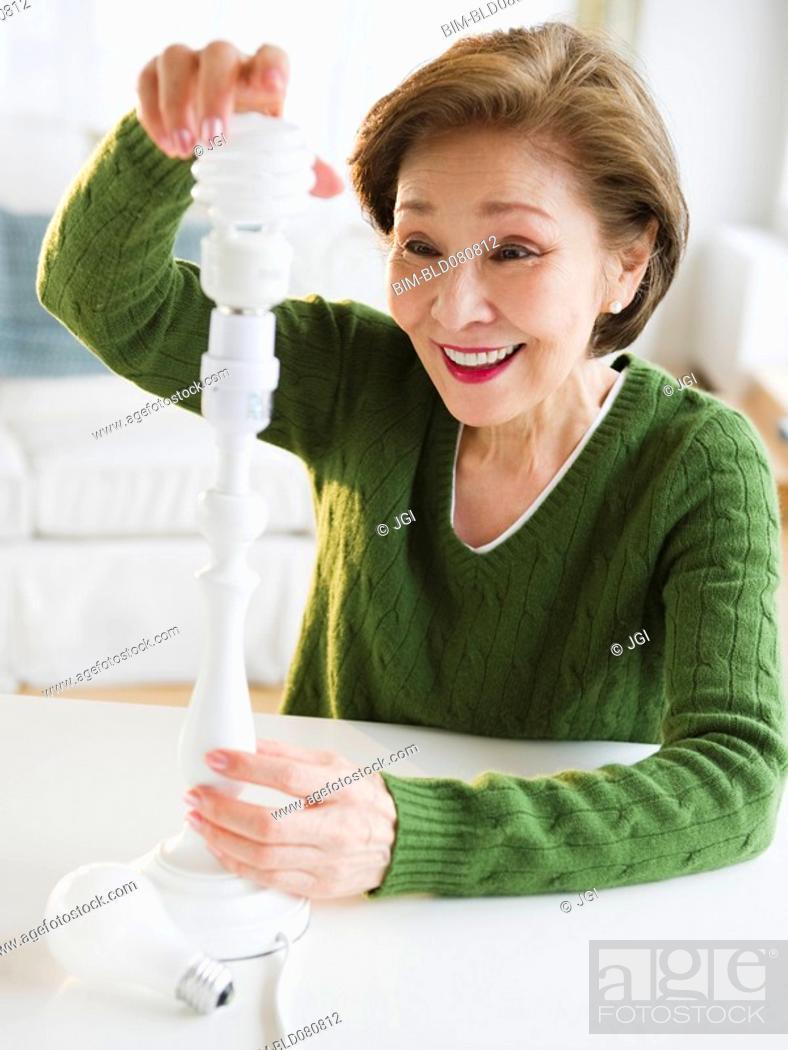 Stock Photo: Japanese woman replacing energy efficient light bulb.