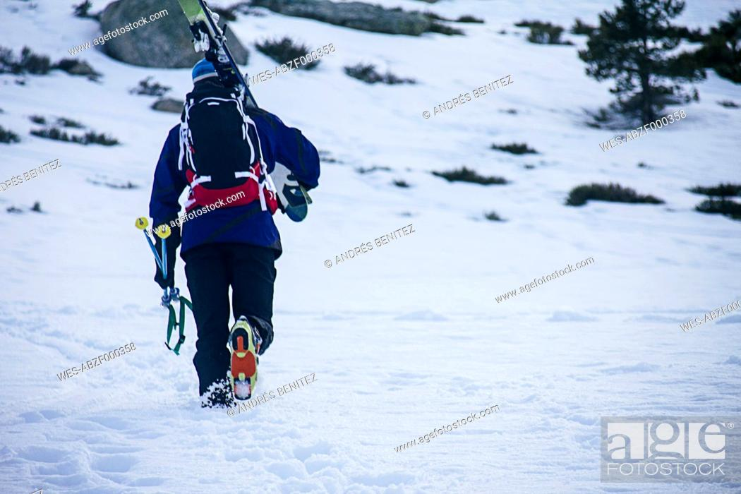 Stock Photo: Man with skis and backpack walking in snow.