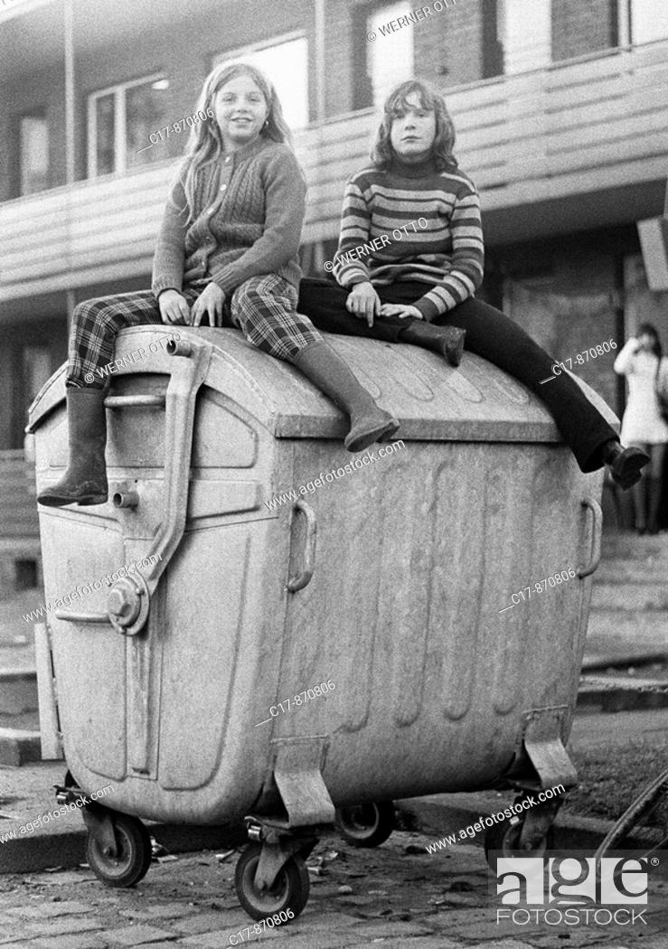 Imagen: Seventies, black and white photo, people, children, two girls sitting on a refuse container, street kids, aged 10 to 13 years.