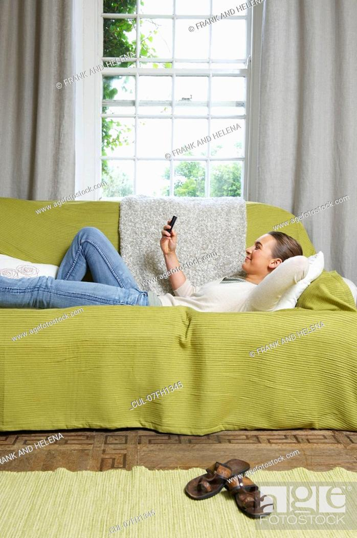 Stock Photo: Young woman texting on couch.