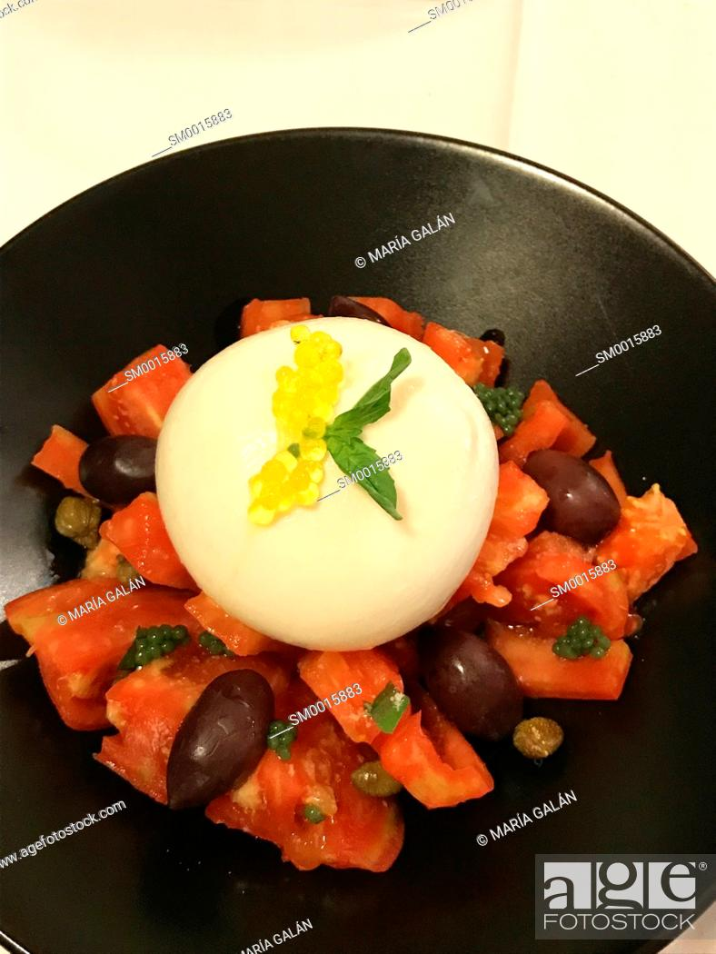 Stock Photo: Tomato salad with black olives, cottage cheese and olive oil pearls.