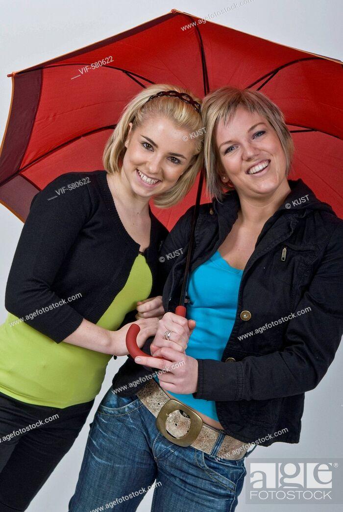 Imagen: zwei junge Frauen unter rotem Regenschirm - Niederoesterreich, Ísterreich, 26/11/2007.