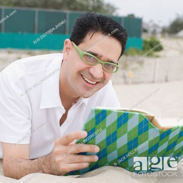Stock Photo: Portrait of a mature man lying on sand and holding a book.
