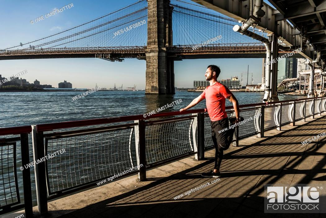 Photo de stock: USA, New York City, sportive man stretching at East River.