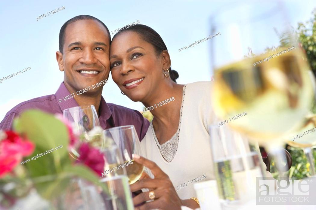 Stock Photo: Elegant couple cheek to cheek holding wine glasses at garden party table.