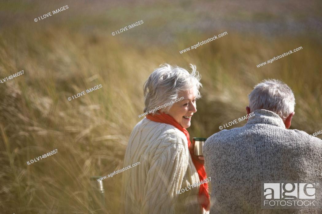 Stock Photo: A senior couple sitting amongst the sand dunes, talking.
