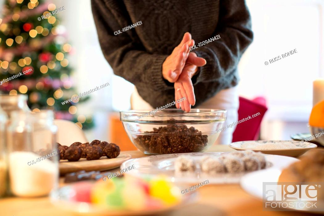 Photo de stock: Preparing christmas (chocolate, coconut, oat) truffles at kitchen counter.