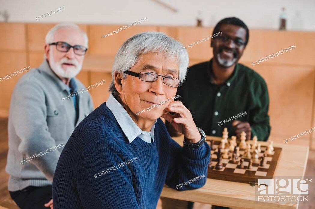 Stock Photo: group of happy senior friends playing chess together.
