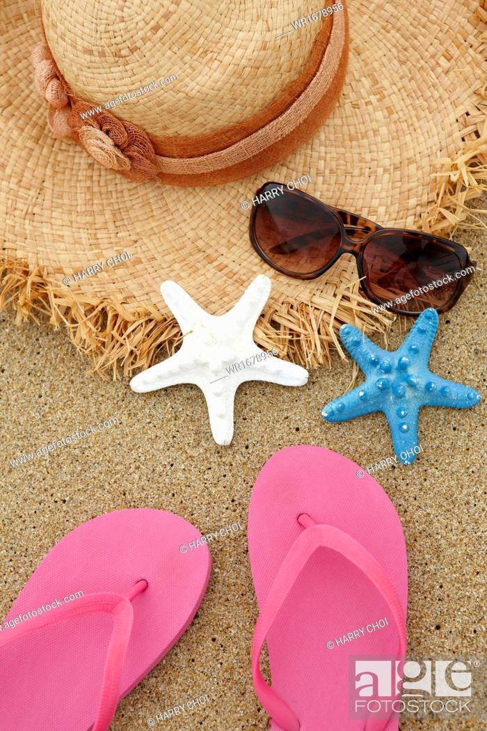 Stock Photo: a pair of flip flops and other items on a beach.
