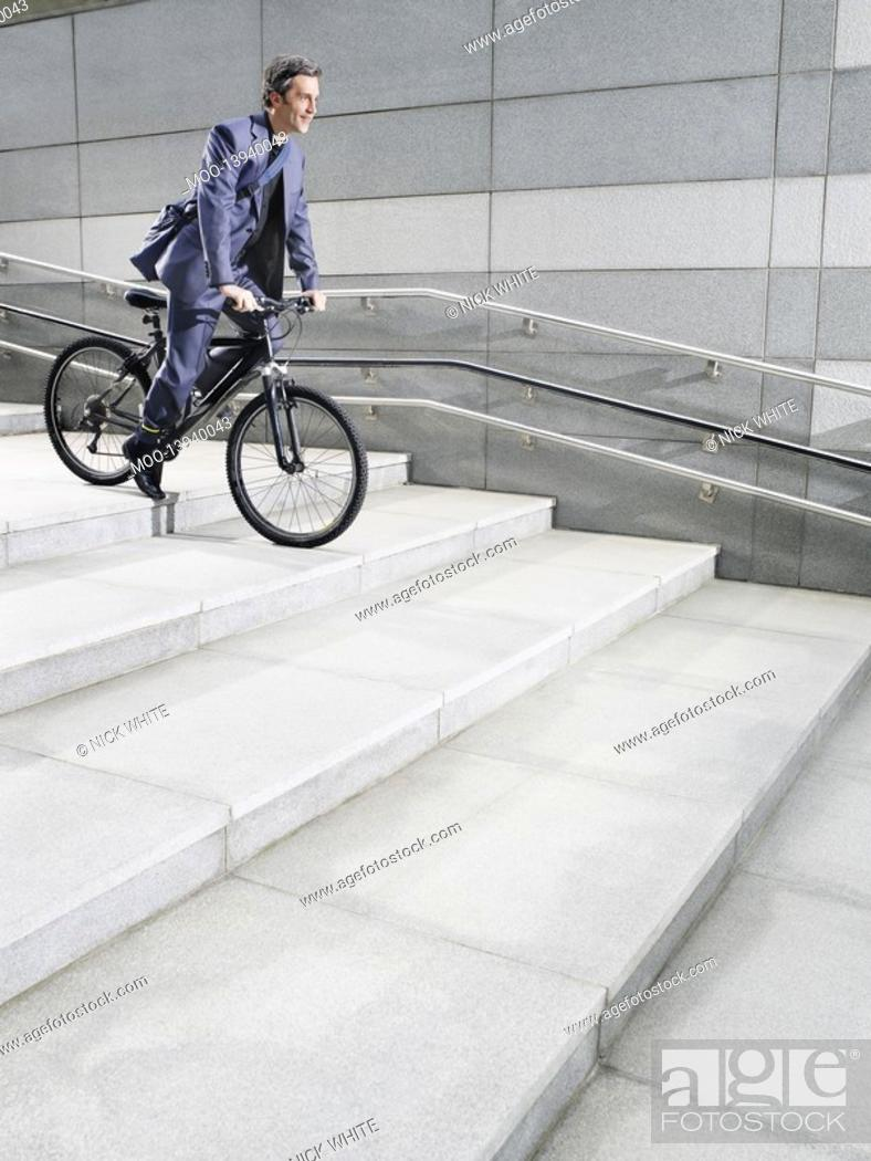 Stock Photo: Business man riding bicycle down steps side view.