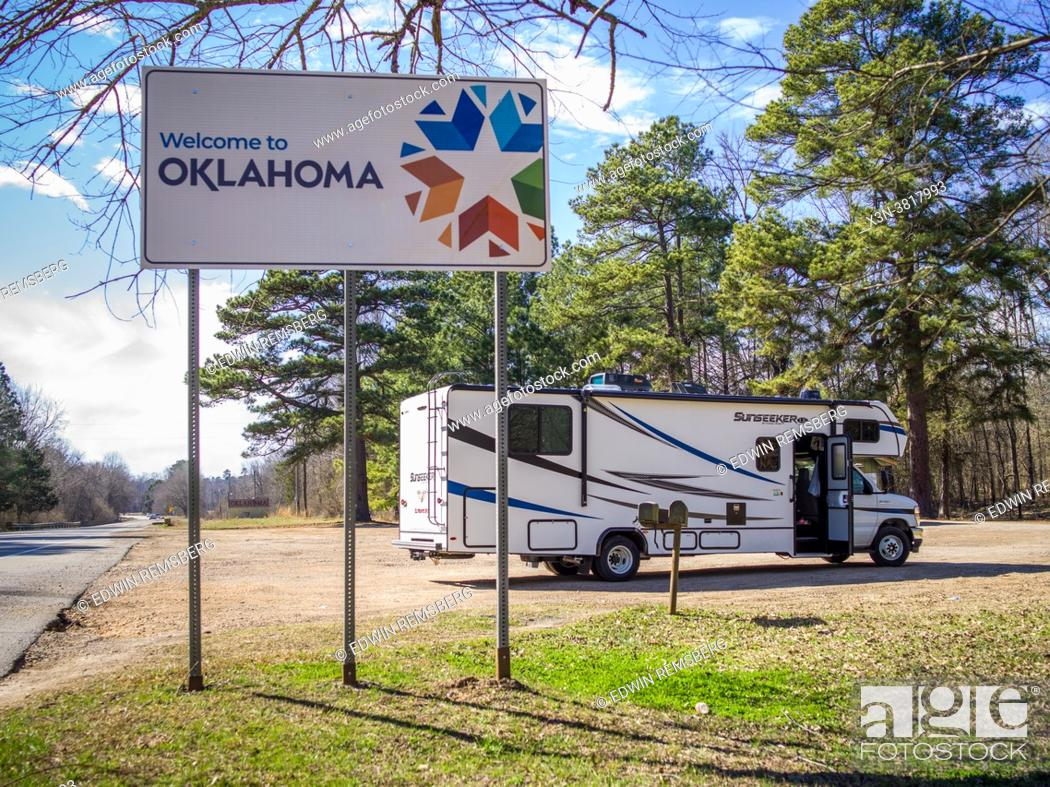 Stock Photo: Road-sign welcomes those entering into Oklahoma with RV sitting in parking lot behind it, Oklahoma.