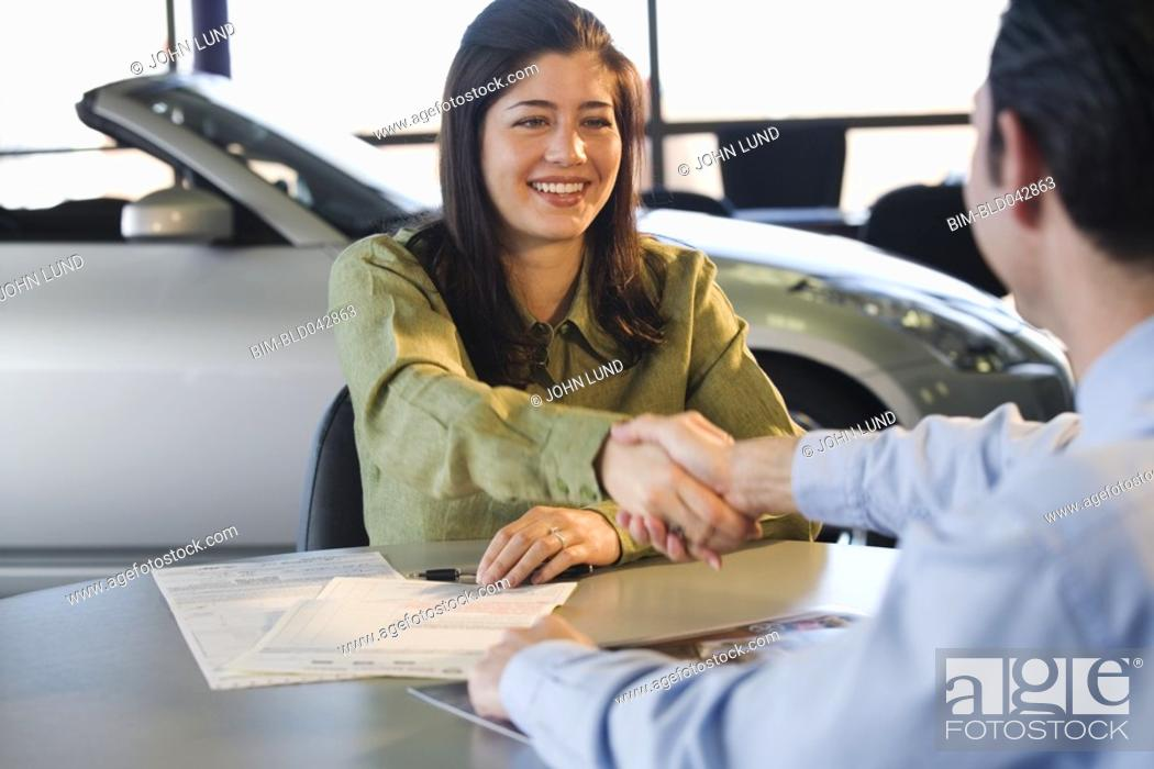 Stock Photo: Woman shaking hands with car salesman.