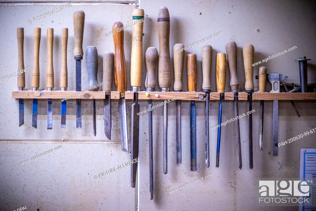 "Stock Photo: 22 June 2020, Mecklenburg-Western Pomerania, Rostock: Tools for woodworking hang in the workshop """"Historical keyboard instruments - Johann-Gottfried Schmidt""""."