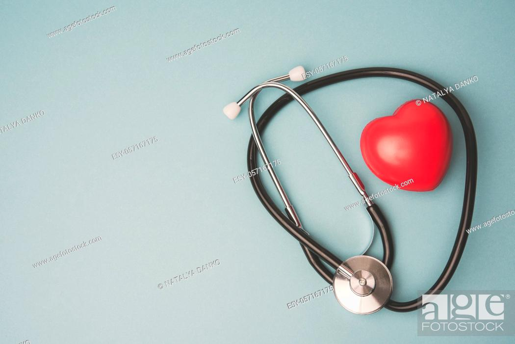 Stock Photo: medical stethoscope and red rubber heart on blue background, top view.